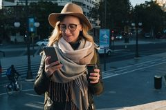 Sunny autumn day. Young attractive woman tourist in hat and eyeglasses stands on city street, uses smartphone stock images
