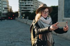 Sunny autumn day. Young attractive woman travels in hat and eyeglasses stands on city street, uses smartphone. And drinks coffee. Hipster girl is looking for Stock Photography