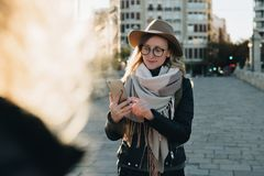 Sunny autumn day. Young attractive woman travels in hat and eyeglasses stands on city street, uses smartphone. And drinks coffee. Hipster girl is looking for Royalty Free Stock Photos