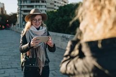 Sunny autumn day. Young attractive woman travels in hat and eyeglasses stands on city street, uses smartphone Stock Photos