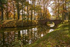 Sunny autumn landscape - a park in golden colors, a waterway with picturesque bridge, yellowed leaves dominate in the picture. Park, sunny afternoon. Autumn stock image