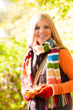 Sunny autumn smiling girl holding dry leaves Stock Photography