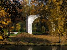 Sunny autumn with yellow trees and a brick arch in the park of Tsaritsyno in Moscow stock photos