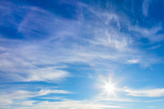 Sunny background of blue sky with real sun and light clouds Stock Photos