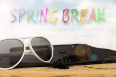 Sunny background with the word spring break. Sunny background with mortarboard, sun glasses, and the word spring break royalty free stock photos