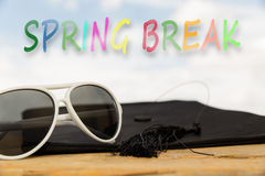 Sunny background with the word spring break. Sunny background with mortarboard, sun glasses and the word spring break royalty free stock photography