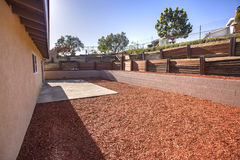 Sunny backyard with wood chips and wood terraces in sunny San Diego California Stock Photos