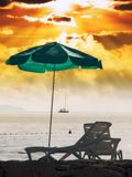 Sunny beach. Beach chair and umbrella on the beach under red sky Stock Images