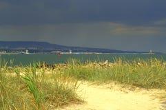 Sunny beach against darken coast Royalty Free Stock Photography