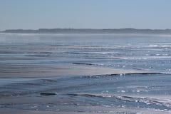 Sunny beach. The coast of northumberland. the tide going out under a deep blue sky. a slight haze  sandy beach Stock Images