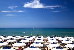 Sunny Beach com os guarda-chuvas brancos e azuis em Itália foto de stock