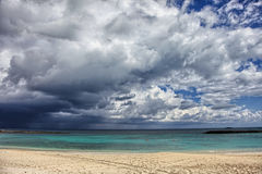 Sunny beach, dark clouds and turquoise water. Paradise Island, Bahamas Royalty Free Stock Image