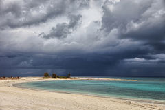 Sunny beach, dark clouds and turquoise water. Paradise Island, Bahamas Royalty Free Stock Photos