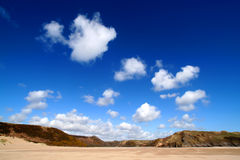 Sunny beach landscape. White fluffy clouds against deep blue sky above three cliff bay in the gower peninsula, south wales, UK royalty free stock image