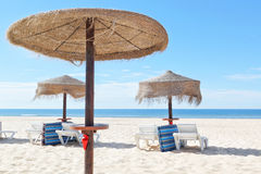 Sunny beach in Portugal with wooden umbrellas near the sea. Stock Image