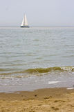 Sunny beach with sailing boat in distance Stock Photos