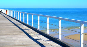 Sunny beach scene from jetty point of view. Stock Images