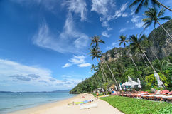 Sunny Beach at the seaside with palm trees and stunning karst formation. Beauty of nature Stock Images