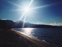 Sunny beach. Sun shining on a beach and ocean water Stock Image