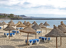 Sunny beach with sunbeds and parasols. A sunny beach on the island of tenerife with sunbeds and parasols ans a nice view Stock Photography