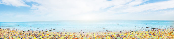 Sunny beach with sunshade on blue cloudy sky Royalty Free Stock Photo