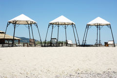 Sunny beach with 3 tents. 3 tents standing next to each other at the beach Royalty Free Stock Photo