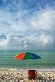 Sunny beach and umbrella Stock Photography