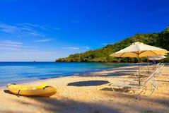 Sunny Beach Vacation Destination. Kayak & Umbrellas stock photography