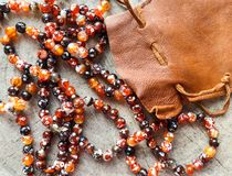 Sunny beads of amber fireplace faceted agate with leather jewelry pouch bag on rustic background stock photography