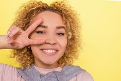 Sunny and beautiful girl is looking on the camera and smiling. She is showing the piece symbol with her fingers and hold royalty free stock photos