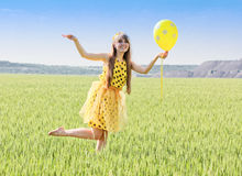 Sunny, beautiful, smiling girl with long blond hair on a green f Royalty Free Stock Image