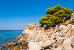 Sunny beautiful summer sea view with Greek blue sea and shallow clear water with small rocks, Halkidiki Greece stock photography
