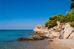 Sunny beautiful summer sea view with Greek blue sea and shallow clear water with small rocks, Halkidiki Greece stock photos