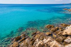 Sunny beautiful summer sea view with Greek blue sea and shallow clear water with small rocks, Halkidiki Greece royalty free stock photography