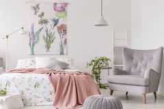 A sunny bedroom interior with a bed dressed in green pattern white linen and a peach blanket. Gray comfortable armchair beside the. Bed and a textile print of stock photography