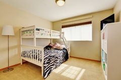 Sunny beige kids` room with bunk bed stock image