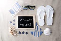 Sunny Blackboard On Sand, Sommerferien Means Summer Holidays Stock Photos