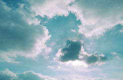 Sunny blue sky with white clouds. The sun is hidden behind the clouds Royalty Free Stock Images