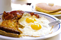 Sunny breakfast. Two roasted eggs with fried ham Royalty Free Stock Photos