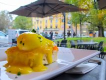 Sunny breakfast with bread toast, salmon and poached egg with greens on a rainy day in Italy royalty free stock photos