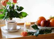 Sunny Breakfast Tray. Breakfast tray with fruit, coffee, candle and beautiful orange and yellow roses; oof bouquet in background Stock Photography