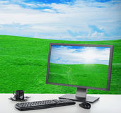 Sunny bright office. Computer desk in a bright office under a beautiful sky on a green meadow with grass royalty free stock images