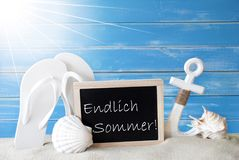 Sunny Card With Endlich Sommer Means Happy Summer. Chalkboard With German Text  Endlich Sommer Means Happy Summer. Blue Wooden Background. Sunny Summer Card With Stock Photography