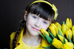 Sunny child girl with bouquet of yellow tulips Stock Images