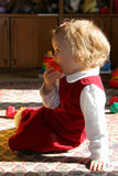 Sunny child's room. Little baby in sunlight sitting on the floor with her toy Royalty Free Stock Image