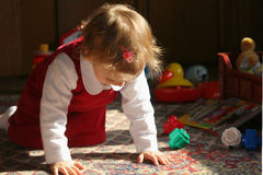 Sunny child's room. Little baby in sunlight playing on the floor Royalty Free Stock Photography