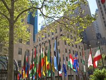Sunny City. This is a colorful shot of the flags and park like setting of Rockefeller Center in New York stock image