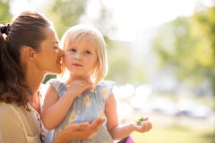In a sunny city park, a mother with daughter. In a sunny city park, a mother whispers loving words of encouragement into her blonde, blue-eyed daughters ear. You royalty free stock image