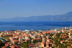 Sunny cityscape of Rijeka, Croatia, with blue Adriatic Sea. Sunny cityscape of Rijeka, the largest port of Croatia, with red rooftops of city center and the blue Stock Photography