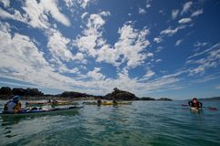 Sunny, cloud covered sky, green ocean and colorful kayaks drift in calm water near the Brookes Peninsula stock photos
